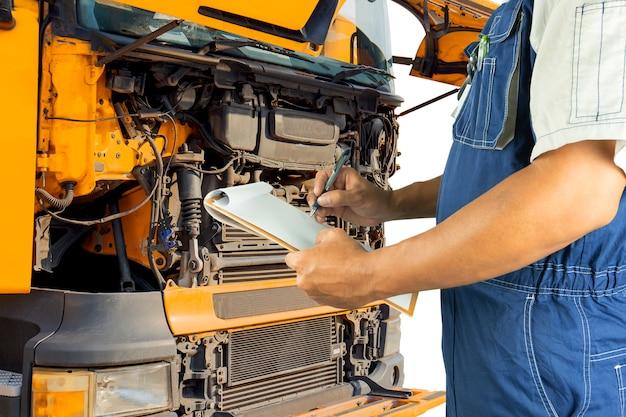Automechaniker, der das klemmbrett kontrolliert den motor eines lkw hält.