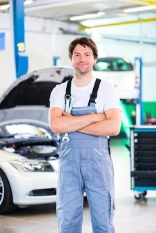 Automechaniker, der den automotor in der werkstatt repariert