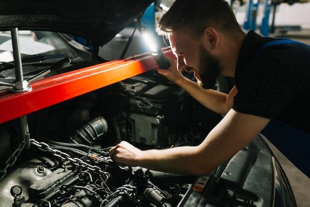 Automechaniker, der den motor des autos schaut