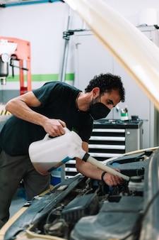 Automechaniker, der den ölstand mit chirurgischer maske überprüft