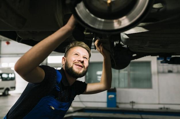 Automechaniker, der die bilge des autos schaut