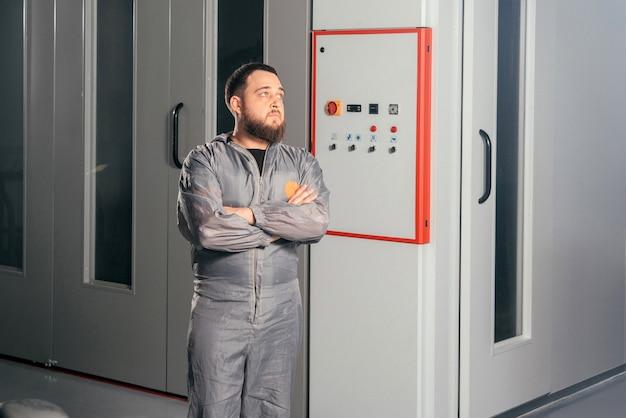 Automechaniker, der die lackierkamera in einer autoreparaturstation betätigt, die knöpfe drückt