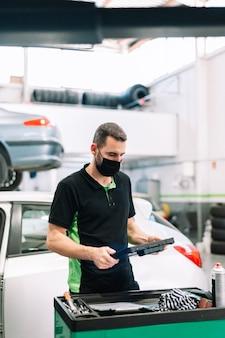 Automechaniker, der die zwischenablage mit chirurgischer maske hält und das wartungsfahrzeug überprüft