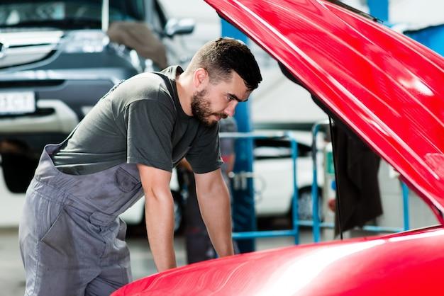 Automechaniker, der in der garage arbeitet. reparaturservice, der den motor des autos betrachtet.