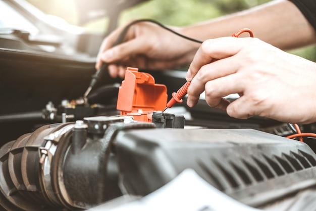 Automechaniker, der in der garage arbeitet techniker hände des automechanikers, der in der autoreparatur arbeitet