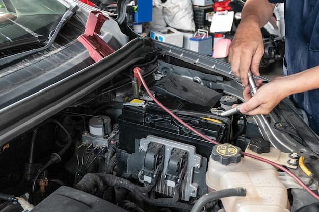 Automechaniker, der in einem auto repariert