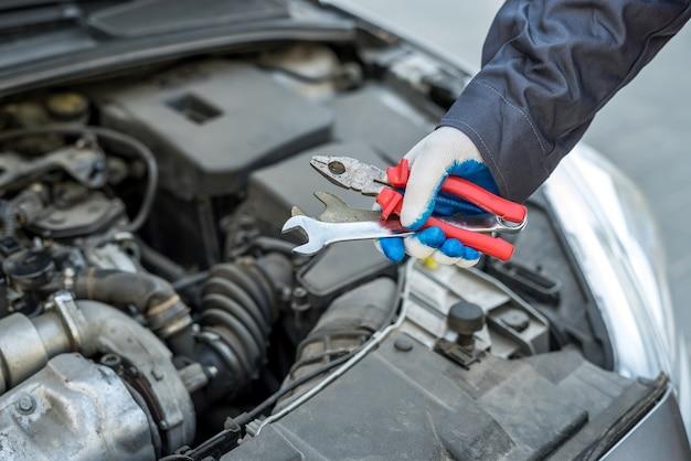Automechaniker, der mit schlüsselschlüssel in der autoreparatur arbeitet, nahaufnahme