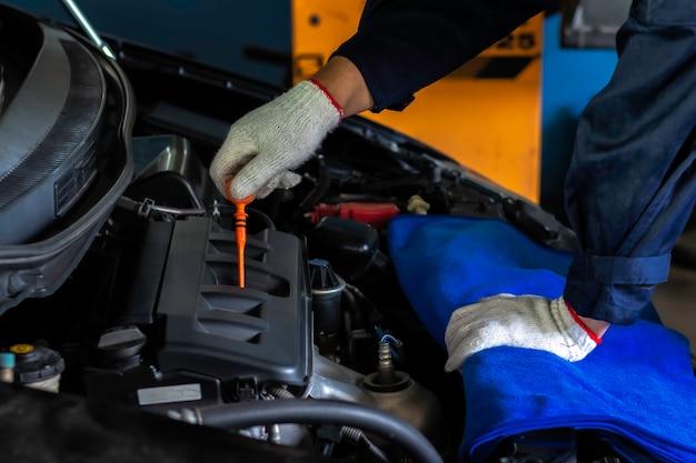 Automechaniker, der motoröl auf wartung überprüft