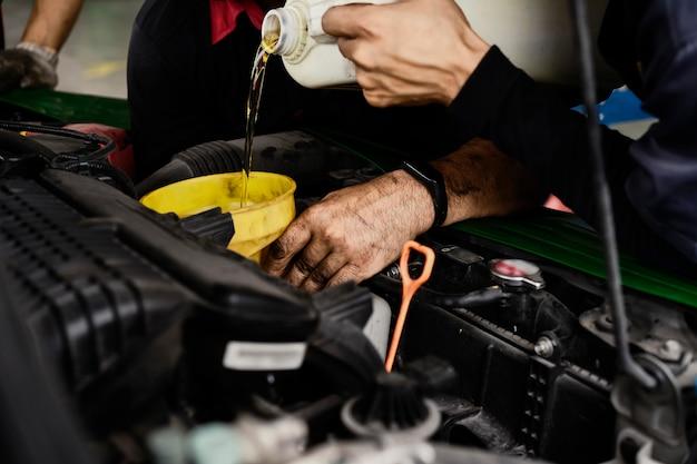 Automechaniker, der ölmaschine ändert. der mann wechselt das motoröl. motoröl wechseln. autoölwechsel. prüfen sie das service-center für autowartung. transportreparatur