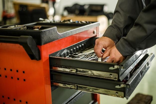 Automechaniker, der werkzeuge vom werkzeugkasten herausnimmt.