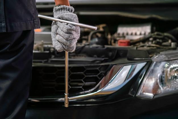 Automechaniker, der zum motor in der garage schaut. service auto motor reparieren.