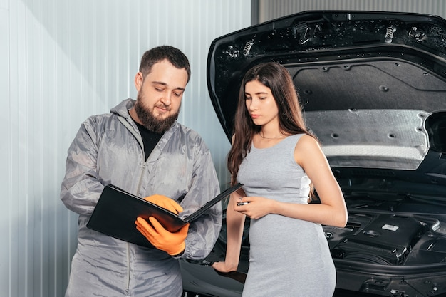 Automechaniker erklärt der kundin die rechnung für die fahrzeugreparatur und unterschreibt die papiere