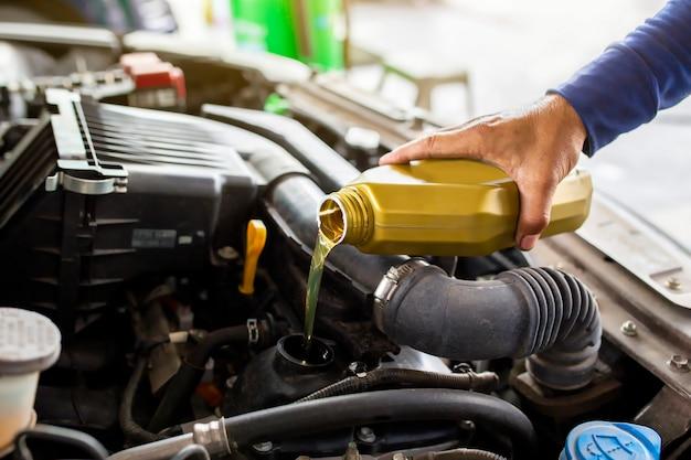Automechaniker ersetzen und gießen frisches öl in den motor an der wartungsreparatur-servicestation.
