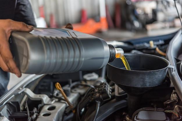 Automechaniker füllt ein frisches schmiermittelmotoröl