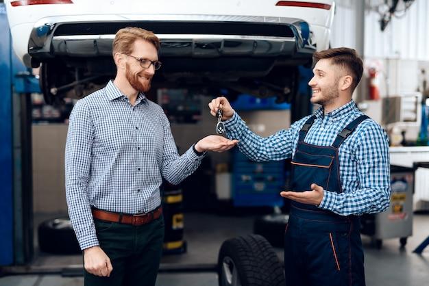 Automechaniker gibt dem erfüllten kunden autoschlüssel.