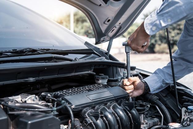 Automechaniker hände mit schraubenschlüssel, um einen automotor zu reparieren
