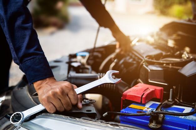 Automechaniker hände mit schraubenschlüssel zur reparatur und überprüfung eines automotorsystems.