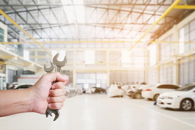Automechaniker-hand, die schraubenschlüssel über autoreparatur-service-center-garage hält