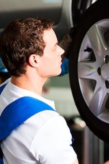 Automechaniker in änderndem reifen der werkstatt