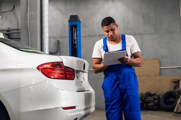Automechaniker in arbeitskleidung inspiziert ein auto in einer werkstatt