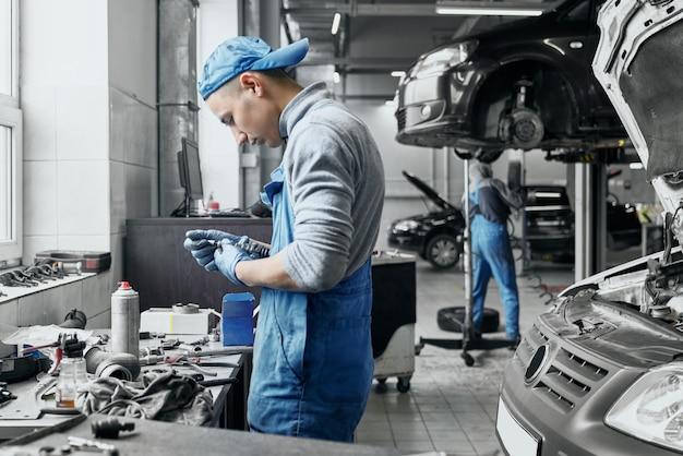 Automechaniker in overalls arbeiten daran, alte zündkerzen zu wechseln