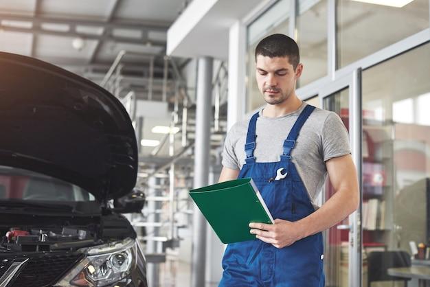 Automechaniker mann oder schmied mit zwischenablage in der werkstatt.