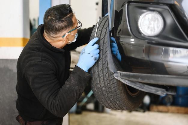 Automechaniker mit gesichtsmaske, die an autowerkstatt arbeitet.
