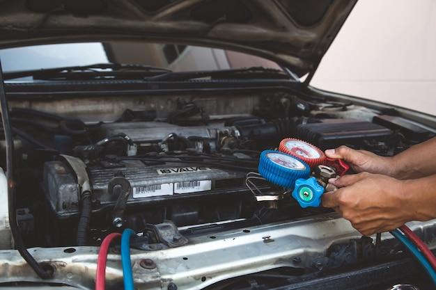 Automechaniker mit messgeräten zum befüllen von autoklimaanlagen.