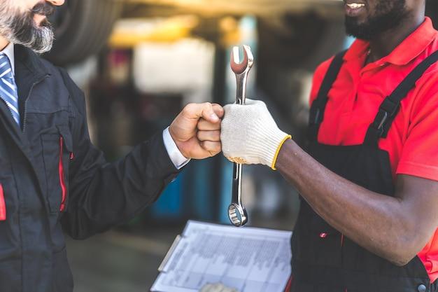Automechaniker mit schraubenschlüssel in der hand. würgegriff. nahaufnahme autoreparatur schwarzer mann hand und kaukasischer mann kunde.