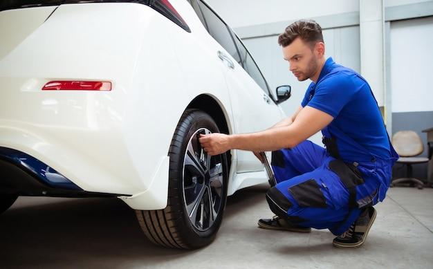 Automechaniker mit tablet in der hand und arbeitsoverall prüft den zustand der reifen nach dem wechsel