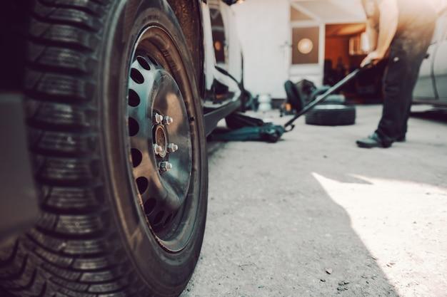 Automechaniker mit wagenheber in der werkstatt. selektiver fokus im reifen.