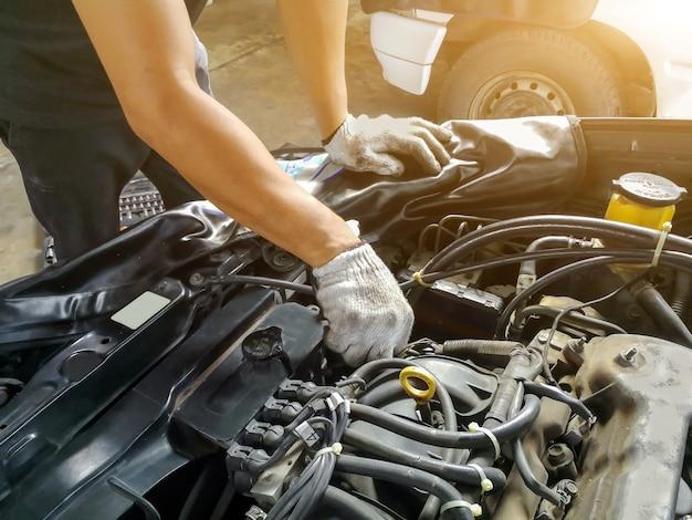 Automechaniker mit werkzeugfunktion prüfen und einen alten automotor an der tankstelle reparieren, vor der fahrt wechseln und reparieren