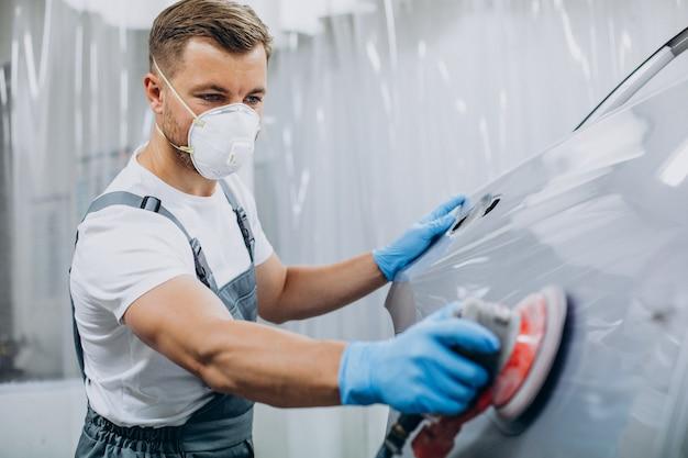 Automechaniker poliert auto vor dem lackieren