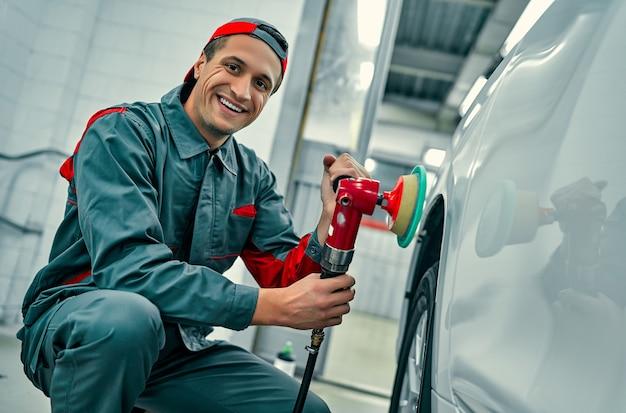 Automechaniker poliert autokarosserie. autoreparatur und wartung.