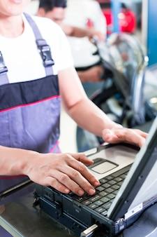 Automechaniker prüft automotor mit diagnosewerkzeug in seiner werkstatt