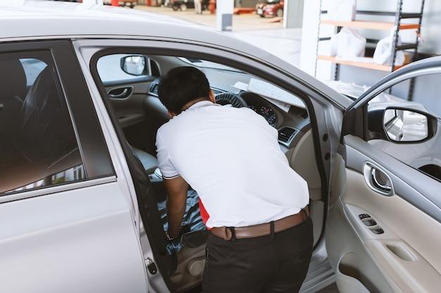 Automechaniker reparaturmann, der ein auto prüft