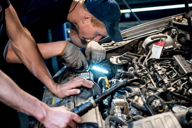 Automechaniker-reparaturmotor an der tankstelle