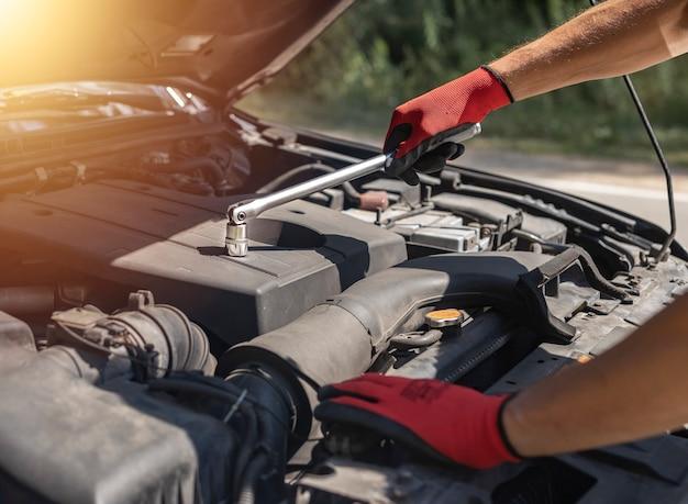 Automechaniker repariert automotor mit schraubenschlüssel und haube auf der straße