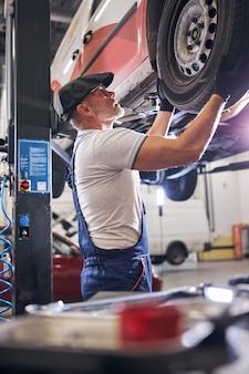 Automechaniker repariert autorad an der tankstelle
