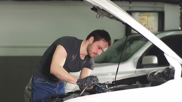 Automechaniker testet elektrisches system am automobil.