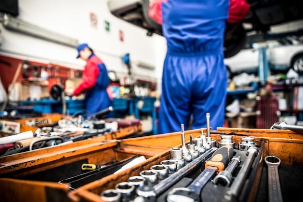 Automechaniker überprüfen den motor - zwei männer arbeiten in einer werkstatt, nahaufnahme an werkzeugen