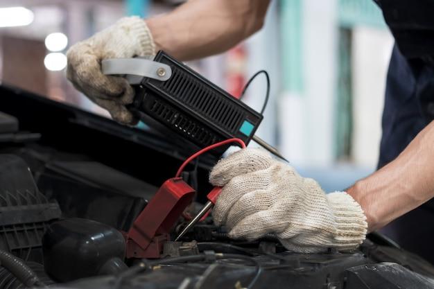 Automechaniker überprüfen die batteriekapazität des fahrzeugs