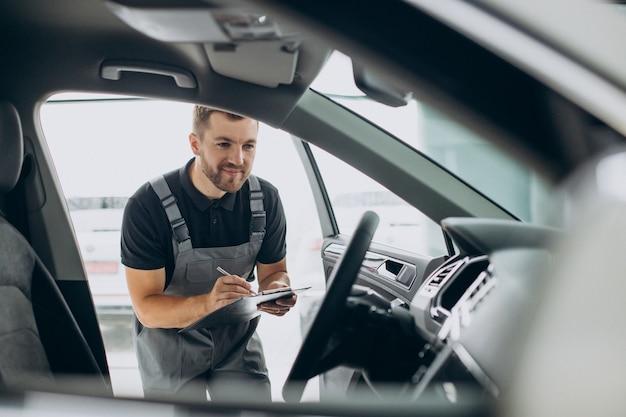 Automechaniker überprüft ein auto bei einer autowerkstatt