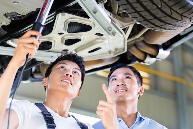 Automechaniker und kunde in der asiatischen autowerkstatt