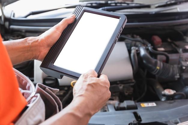 Automechaniker untersuchen auto während der arbeit im autoservice, techniker, der die checkliste für die reparatur des automotors in der garage durchführt