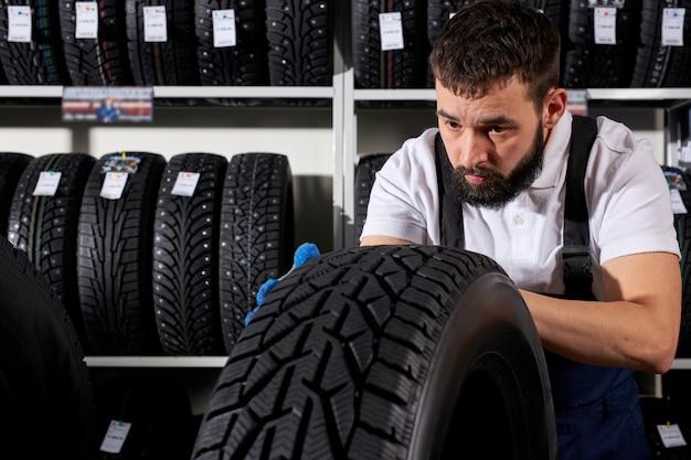 Automechaniker-verkäufer, der reifenoberfläche in seinem geschäft vor dem hintergrund des reifensortiments untersucht. automobil, autos, fahrzeug, transportkonzept