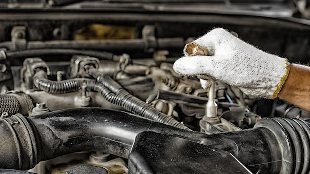 Automechaniker vorbereitung für die arbeit. mechaniker mit edelstahlschlüssel in der hand.