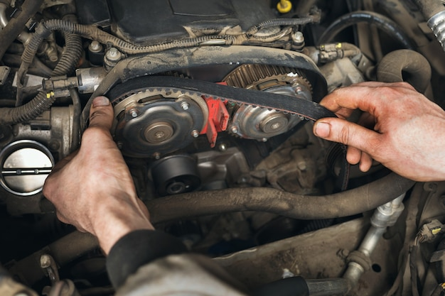 Automechaniker wechselt den zahnriemen im auto, nahaufnahme