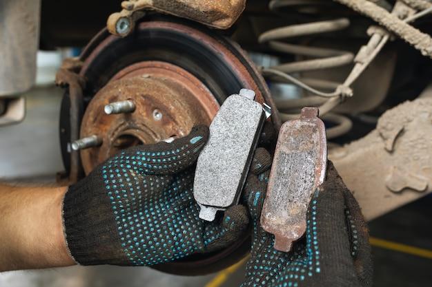Automechaniker zeigt alte und neue bremsbeläge