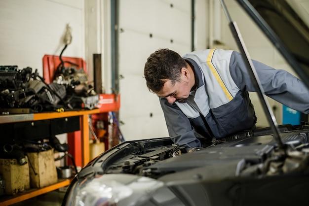 Automechanikermann an der garage, die den motor repariert.